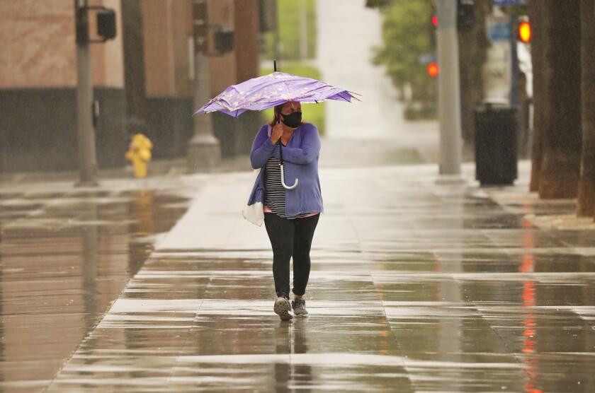 Blanca Torres walks in the rain in downtown Los Angeles in May.