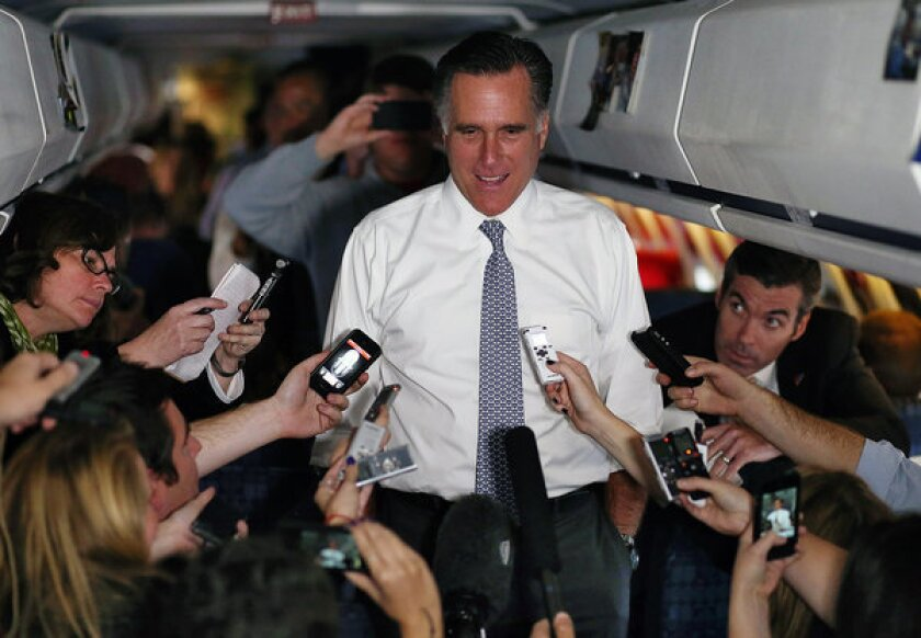 Republican presidential nominee Mitt Romney talks with members of the traveling media aboard his campaign plane en route to Boston.