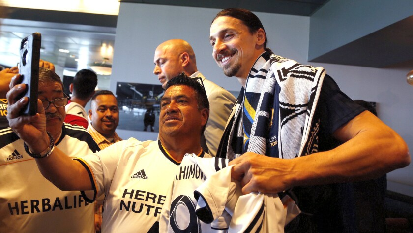 LA Galaxy's newest player Zlatan Ibrahimovic, right, of Sweden, poses with for photos with fans afte