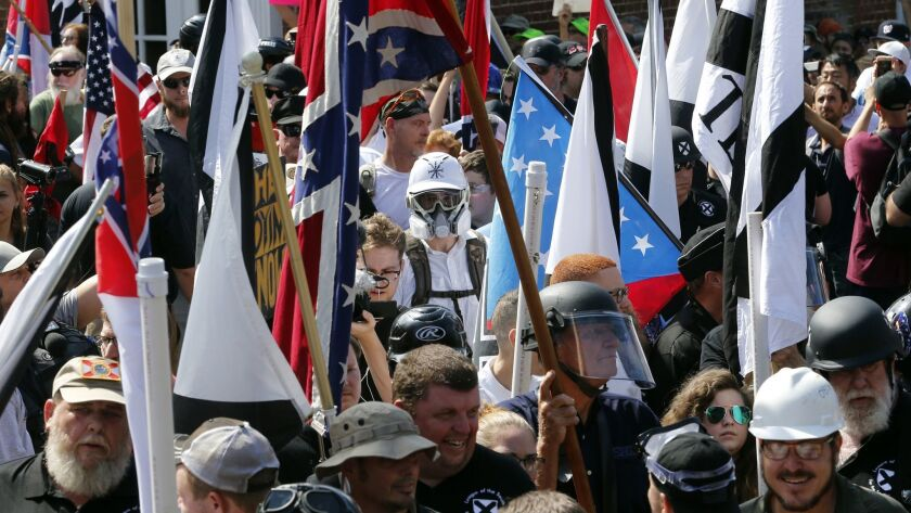 White nationalist demonstrators walk into the entrance of Lee Park surrounded by counter demonstrato
