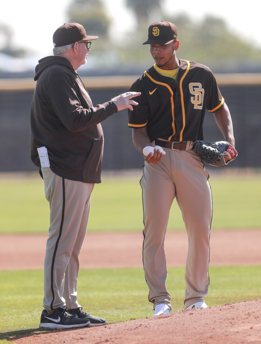 Padres pitcher Luis Patiño talks to pitching coach Larry Rothschild during spring training.