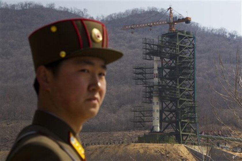 A North Korean soldier stands in front of the country's Unha-3 rocket, slated for liftoff between April 12-16, at a launching site in Tongchang-ri, North Korea on Sunday April 8, 2012. North Korean space officials have moved a long-range rocket into position for this week's controversial satellite launch, vowing Sunday to push ahead with their plans in defiance of international warnings against violating a ban on missile activity.(AP Photo/David Guttenfelder)