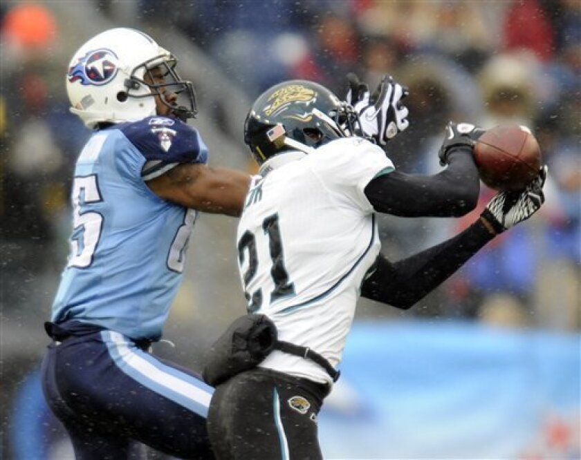 Jacksonville Jaguars cornerback Derek Cox (21) intercepts a pass intended for Tennessee Titans wide receiver Nate Washington (85) in the second quarter of an NFL football game on Sunday, Dec. 5, 2010, in Nashville, Tenn. (AP Photo/Joe Howell)