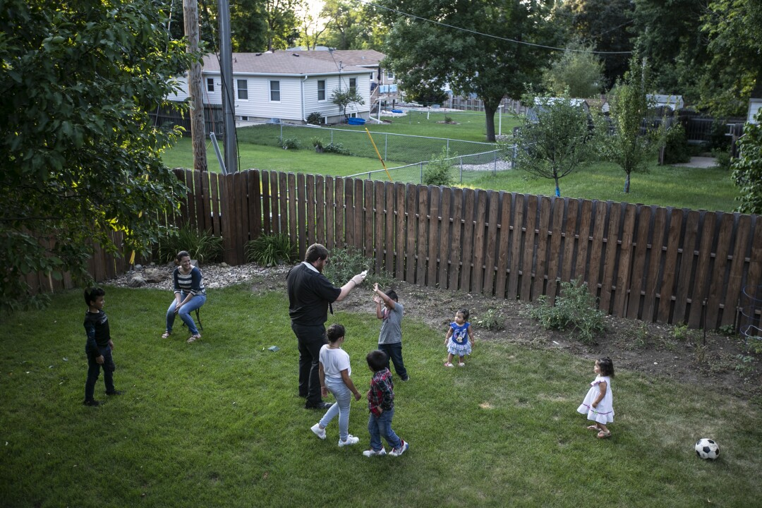 The Rev. Kristopher Cowles slings holy water while blessing the children and the backyard of the Barrera family home.