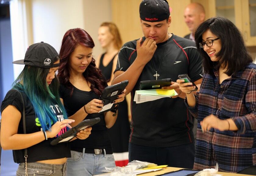 Valley Academy of Arts and Sciences students, from left, Jordann Ventura, 14, Karyna Mills, 15, Guillermo Romero, 15, and Dayanara Trujillo, 15, receive iPads before the start of the school year.
