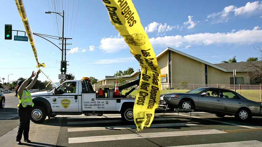 A car is towed away after a woman was shot and killed last August in Pacoima.