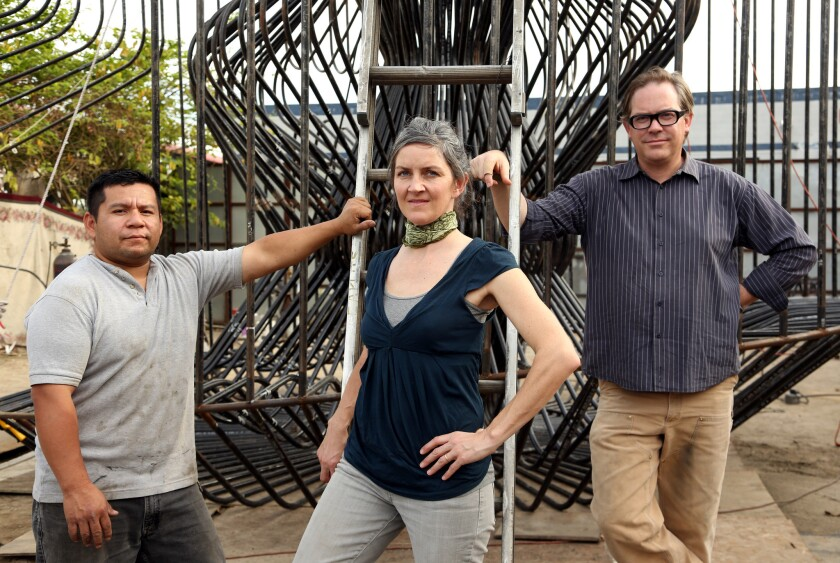 "Lead welder Edwin Ramirez, left, artist Jenna Didier and architect Warren Techentin stand in front of ""La Cage aux Folles,"" a work in progress that will go on exhibit in front of Materials & Applications in April."