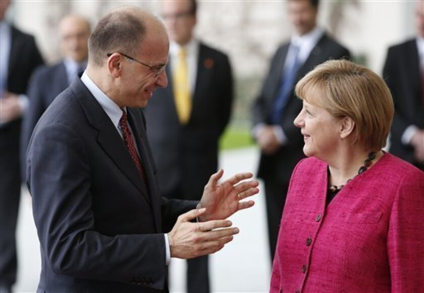 German Chancellor Angela Merkel, right, welcomes the Prime Minister of Italy, Enrico Letta, left, for a meeting at the chancellery in Berlin, Germany, Tuesday, June 30, 2013. (AP Photo/Michael Sohn)