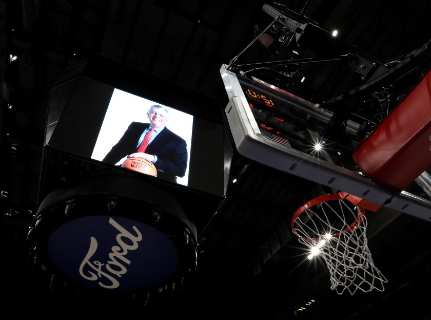 A photo of former NBA commissioner David Stern on the scoreboard, a basketball hoop and the Ford logo can be seen in a photo looking up toward the ceiling of the American Airlines Arena.