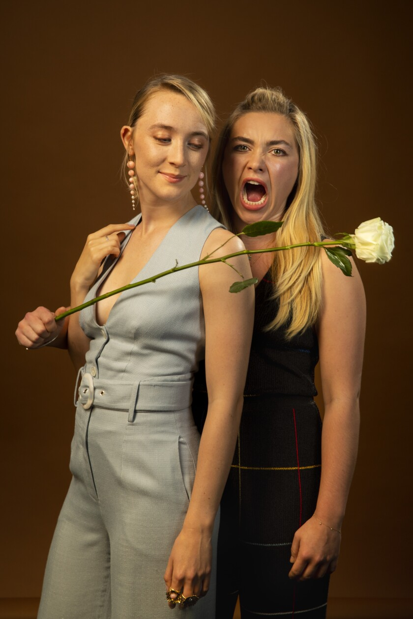 Florence Pugh, right, stands slightly beside and behind Saoirse Ronan, holding a long-stemmed white rose in front of them.
