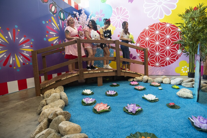 Visitors stand on a bridge in the Tokyo room of the Hello Kitty Friends Around the World Tour pop-up.