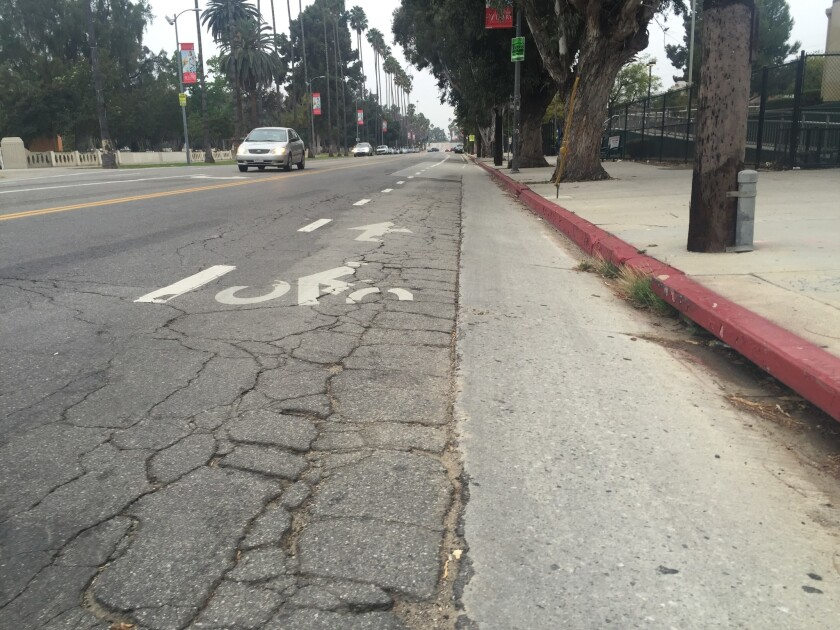A section of the downtown L.A.-bound bike lane on Mission Road, filled with cracks and potholes, is seen across from Lincoln Park on Thursday.