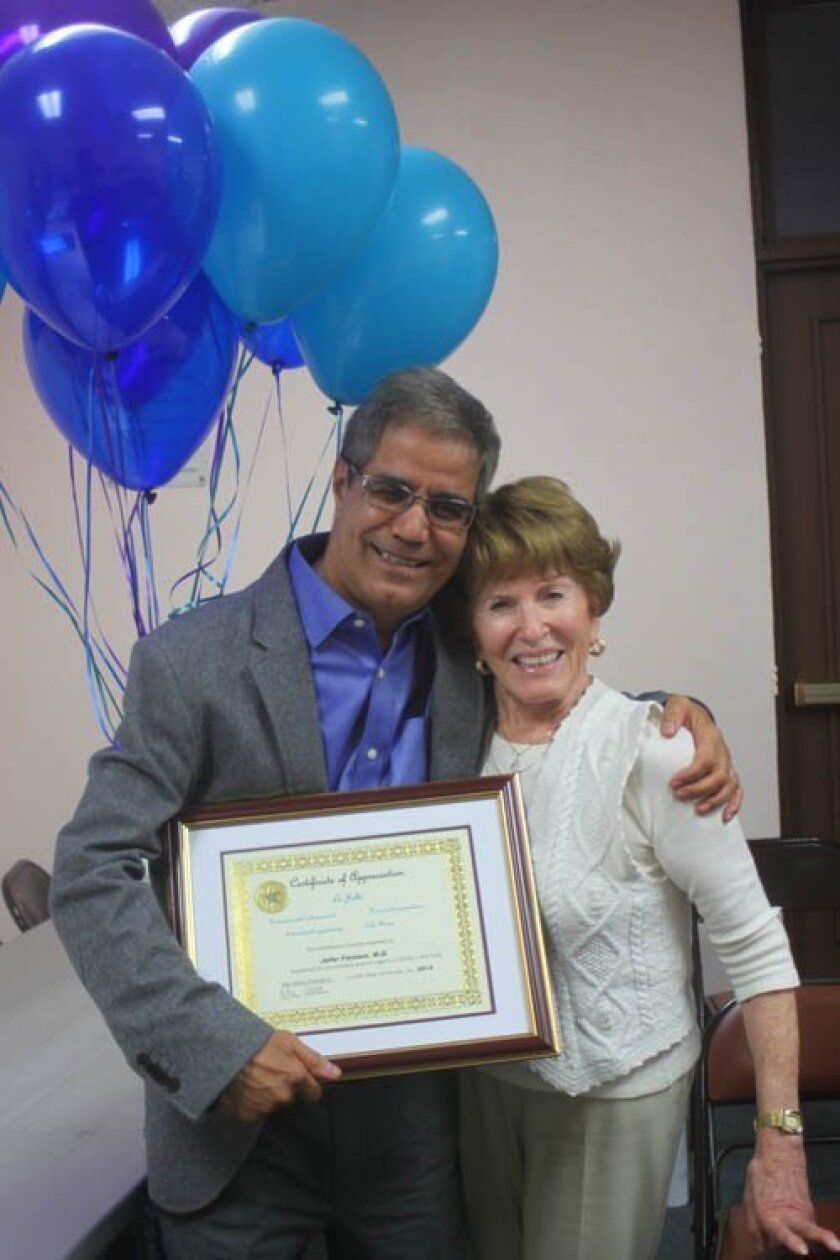 Jafar Farnham with a plaque from Phyllis Minick (right) thanking him for his $35,000 contribution to the Children's Pool Walk beautification project. Ashley Mackin
