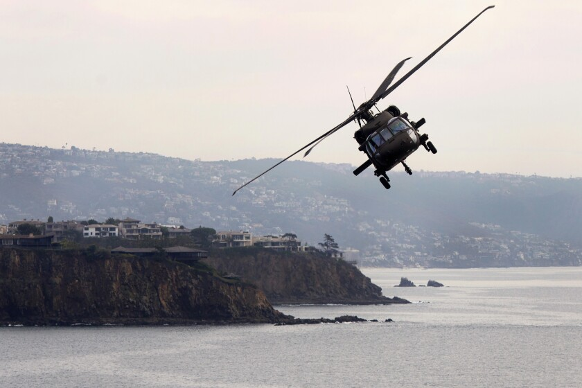 """A UH-60 Blackhawk helicopter flies along the Orange County coast during the California National Guard's annual """"Boss Lift"""" providing free rides to about 80 employers of National Guard soldiers as a thank you for giving them time off work to train and deploy overseas on Friday, December 6, 2019. ///ADDITIONAL INFO: tn-wknd-et-blackhawk-20191206 12/6/19 - Photo by DREW A. KELLEY, CONTRIBUTING PHOTOGRAPHER"""