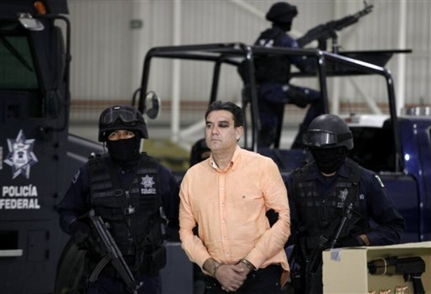 "Police officers escort suspected drug trafficker Manuel Fernandez as he is presented to the media at the federal police headquarters in Mexico City, Monday Nov. 8, 2010. According to federal police Fernandez, an alleged member of the criminal organization led by Joaquin Guzman Loera, aka ""El Chapo Guzman"", was arrested Sunday in the northern city of Culiacan, Sinaloa state. (AP Photo/Eduardo Verdugo)"