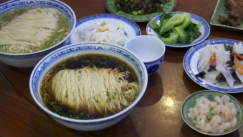 TongDe Xing Noodle Shop serves a tightly woven mound of noodles dropped into a steamy dark broth. It can be ordered with deep-fried fish or simmering pork.