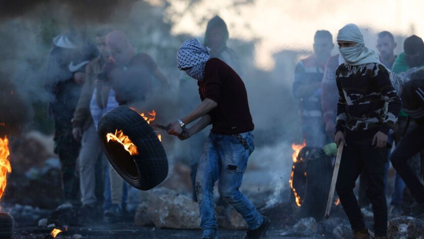 Palestinians burn tires following protests against U.S. President Donald Trump's decision to recogni