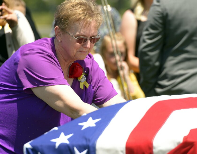 Lorie Ricks lingers for a moment at the casket of her husband, Utah Transit Authority electrician Kay Ricks, 63, who was laid to rest Saturday, May 28, 2016, at Lehi City Cemetery. Ricks served in the Navy and was a veteran of the Vietnam War, 4 years active duty and 2 years in the Naval Reserve an