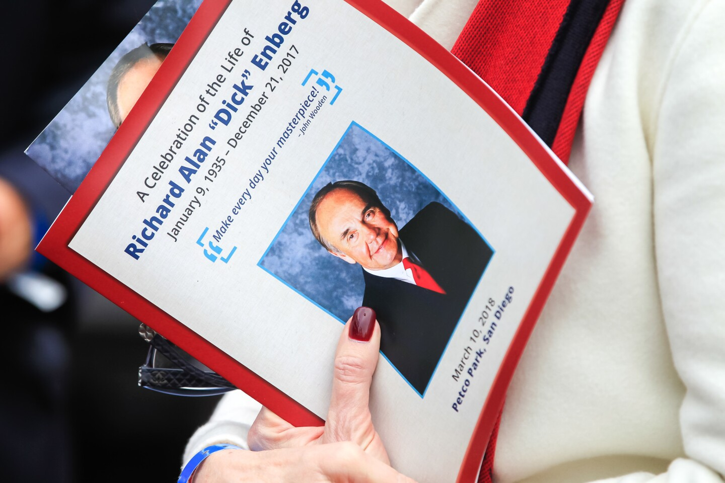 A guest holds a program during the Celebration of Life for Dick Enberg.