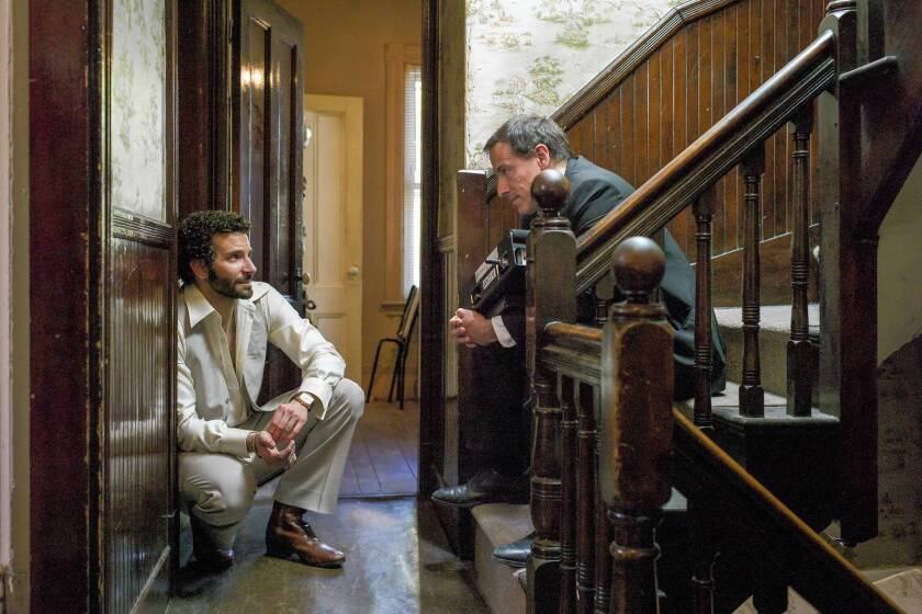 """Bradley Cooper, left, talks with director David O. Russell on the set of """"American Hustle."""""""