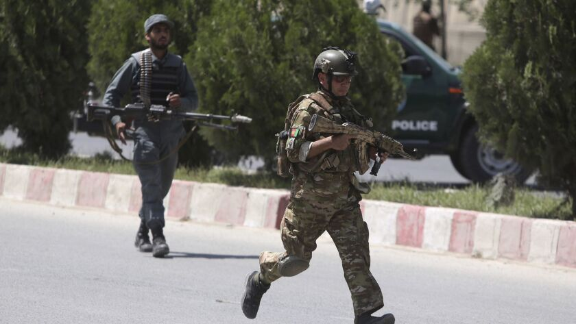 Security personnel arrive at the site of an attack at the Afghan Interior Ministry in Kabul on May 30.