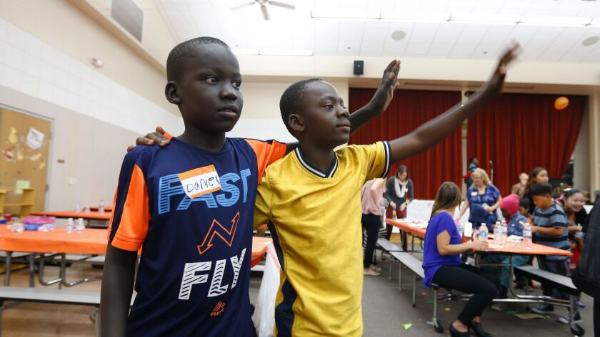Daniel Obang, left, and Innocent Ibrahim, both 11, wave to their friends during a 2017 Thanksgiving meal for refugees and their families put on by San Diego Refugee Tutoring at Ibarra Elementary School.