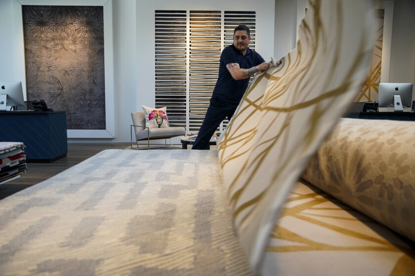 Rug Co. showroom operations manager Javier Garcia, 40,  displays sample rugs during a recent visit.