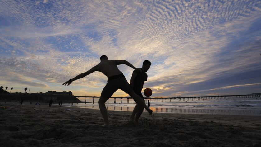 SAN DIEGO, CA 11/16/2017: Visitors from Italy play a game of score on the sand near the Ocean Beach