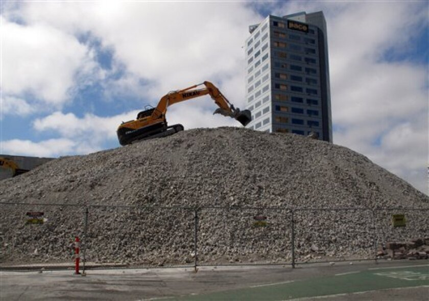 In this Jan. 22, 2013 photo, an excavator climbs the rubble of demolished buildings in downtown Christchurch, New Zealand. The city's population has declined by 13,500, or 3.6 percent, from the 380,000 people it had before the magnitude 6.3 earthquake. Some have left by choice; others because they