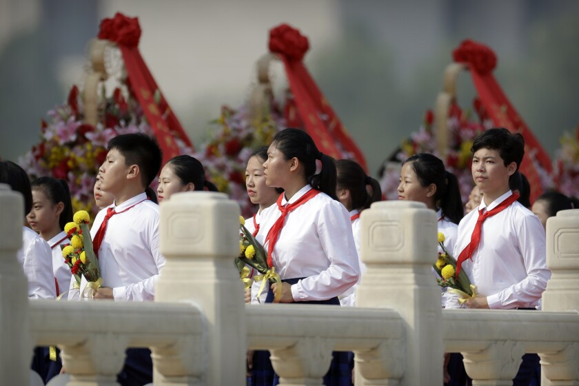 Chinese schoolchildren carry flowers as they walk past wreaths at the Monument to the People's Heroes in Beijing.