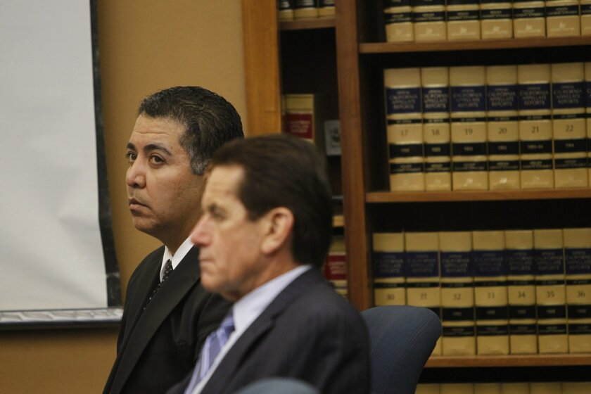 Former San Diego police Officer Anthony Arevalos listens in San Diego Superior Court during his trial on charges that he sexually assaulted women he stopped in the Gaslamp Quarter on suspicion of drunken driving. Jan Ronis, right, is one of his two attorneys.