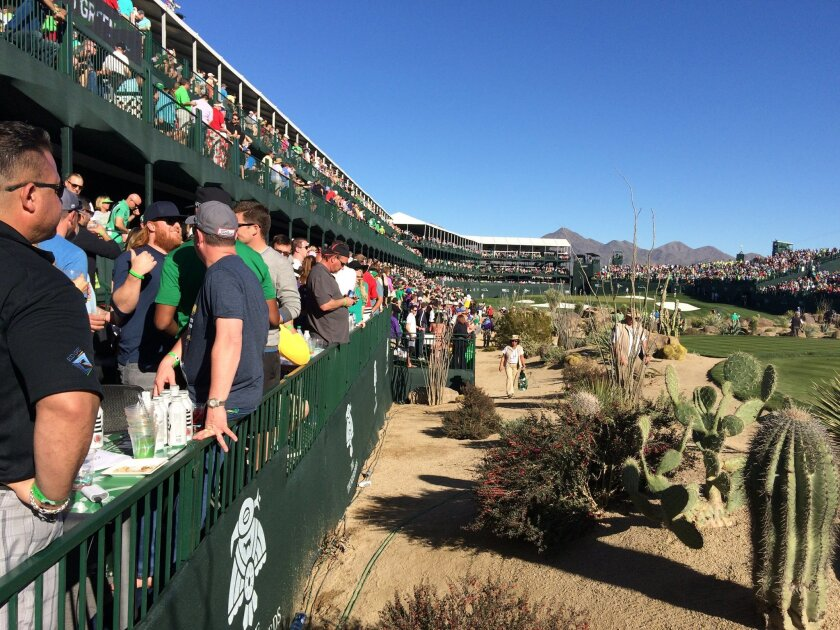 In this Saturday, Feb. 5, 2016, photo, people gather in the grandstand on the 16th hole at TPC Scottsdale, during the third round of the Phoenix Open golf tournament in Scottsdale, Ariz. A picturesque par-3 for 51 weeks, No. 16 at TPC Scottsdale transforms into a golf version of a party cruise the