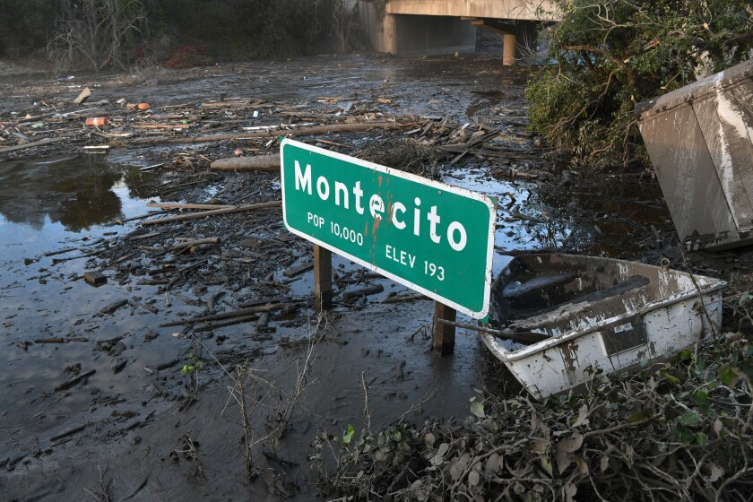 A Montecito freeway sign sits in mud on Highway 101 following the debris flows of late 2017.