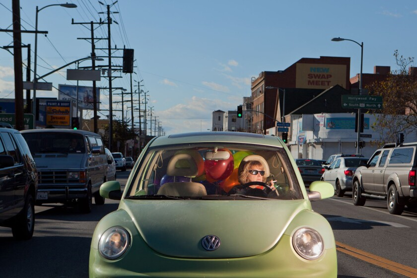A photo on view at the California Museum of Art Thousand Oaks shows a woman at the wheel of a Volkswagen Beetle.
