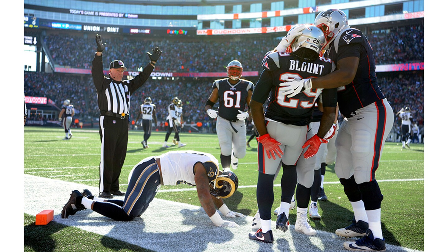 Patriots running back LeGarrette Blount is mobbed by teammates after scoring a touchdown on a 43-yard run against Eugene Sims and the Rams.