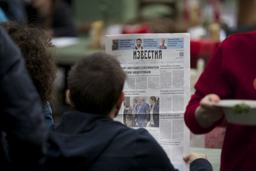 A street cafe visitor reads the Russian newspaper Izvestia with a front-page story about former National Security Agency contractor Edward Snowden.