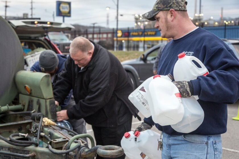 Employees of the South Charleston Public Works Department help residents fill containers with water after the chemical spill in January
