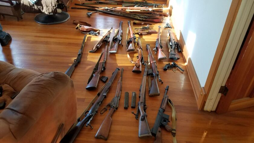 Authorities found and seized dozens of rifles and handguns — some of which are seen here — from Uni