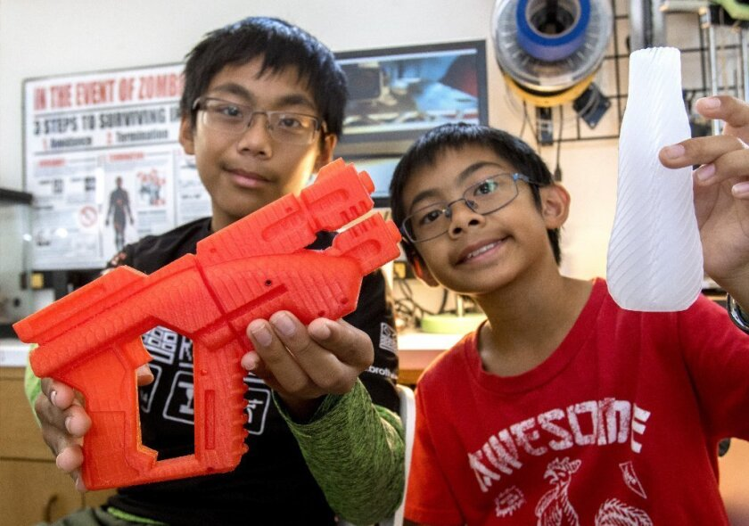 Escondido students Calexis and Calramon Mabalot opened a business making products through 3D printing, including a robotic prosthetic hand. They show a plastic gun designed inspired by the video game Mass Effect and a spiral vase