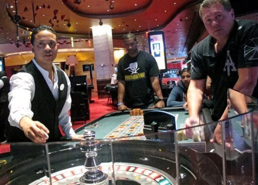 FILE - In this May 21, 2012 file photo, a dealer at Revel prepares for another round of roulette at the Atlantic City, N.J., casino as patrons await the result. Commercial casinos in the U.S. have made it almost all the way back from the hard times of the Great Recession. The American Gaming Association says revenue at non-Indian casinos hit $37.3 billion last year, just a shade under the all-time high reached in 2007. However, New Jersey experienced the largest decline in casino revenue, despit