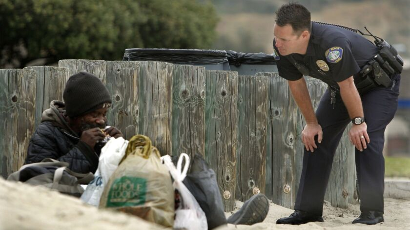 A Laguna Beach police officer talks with a homeless man at Main Beach in this file photo. Laguna and the American Civil Liberties Union reached a settlement this week in a 2015 lawsuit alleging Americans with Disabilities Act violations at the city's night homeless shelter.
