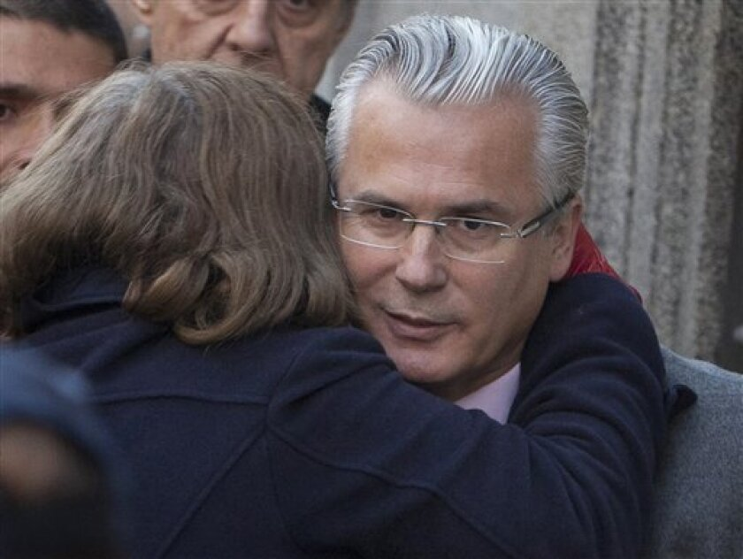 A unidentified woman embraces Spanish judge Baltazar Garzon as he arrives at the Supreme Court in Madrid Tuesday Jan. 31, 2012. Garzon known for pioneering cross-border justice cases is sitting in the dock as a criminal defendant for allegedly overstepping his jurisdiction with a probe of right wing atrocities during and after the Spanish civil war. (AP Photo/Arturo Rodriguez)