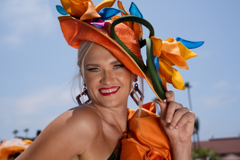 Elena Embree from Alpine wore an orange hat decorated with multicolored scarves at Opening Day at the race track.