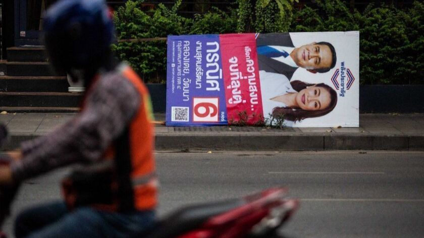 A poster featuring Thai junta leader Prayuth Chan-ocha is taken down in Bangkok after the March 24, 2019, general election.