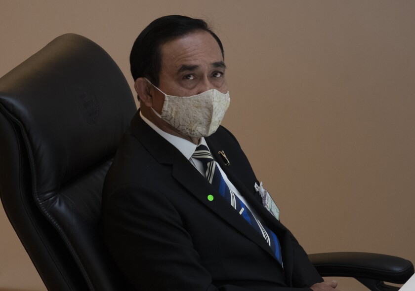 In this Wednesday, May 27, 2020 photo, Thailand Prime Minister Prayuth Chan-ocha wears a face mask to help curb the spread of the coronavirus as he attends an open session at the parliament house in Bangkok, Thailand. Thailand's prime minister has warned his fellow citizens that their nation has handled the health challenges of the coronavirus well, but must pull together to overcome the tremendous damage done to the economy by the pandemic. (AP Photo/Sakchai Lalit)