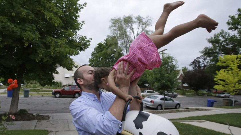 A father plays with his 17-month-old daughter outside their home in Salt Lake City in June 2015.