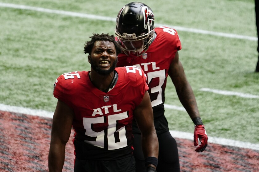 Atlanta Falcons defensive end Dante Fowler Jr. (56) celebrates a goal-line stop of the Detroit Lions during the first half of an NFL football game, Sunday, Oct. 25, 2020, in Atlanta. Fowler was called for unsportsmanlike conduct after a team mate knocked his helmet off during the celebration. (AP Photo/Brynn Anderson)