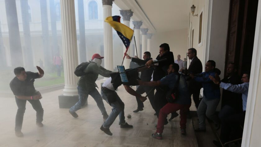 Opposition lawmakers brawl with pro-government militias trying to force their way into the National Assembly during a special session in July.