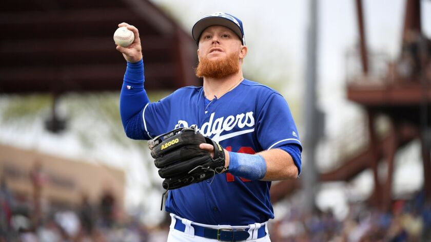 Justin Turner (10) of the Dodgers throws a ball into the stands during a spring training game against the San Francisco Giants at Camelback Ranch on March 11, 2019.