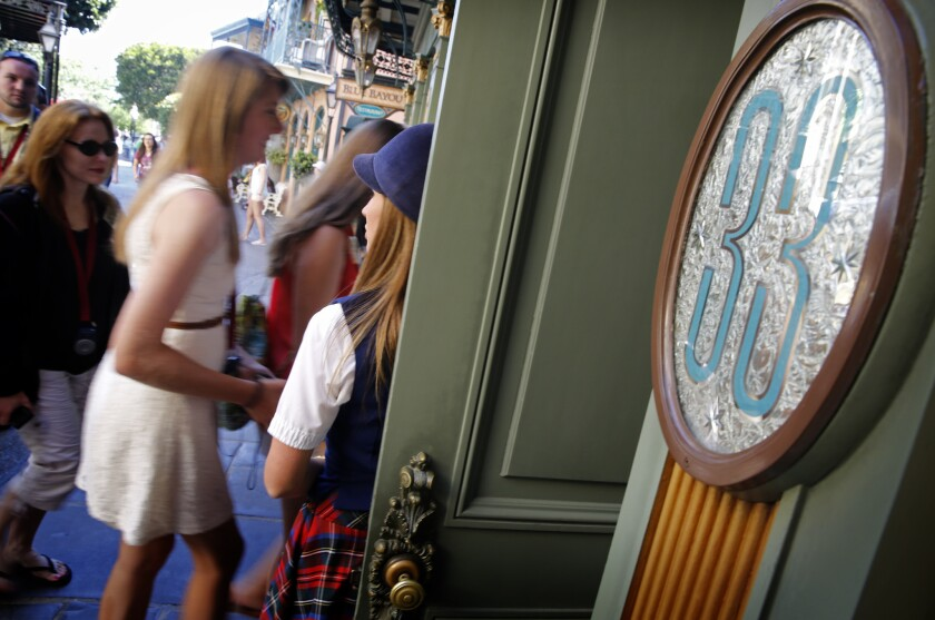 Guest relations guide Victoria Dale holds open the door to Club 33 for visitors on a special VIP tour of Disneyland in Anaheim. A former Club 33 member is suing Disneyland, claiming that his membership was unfairly revoked.